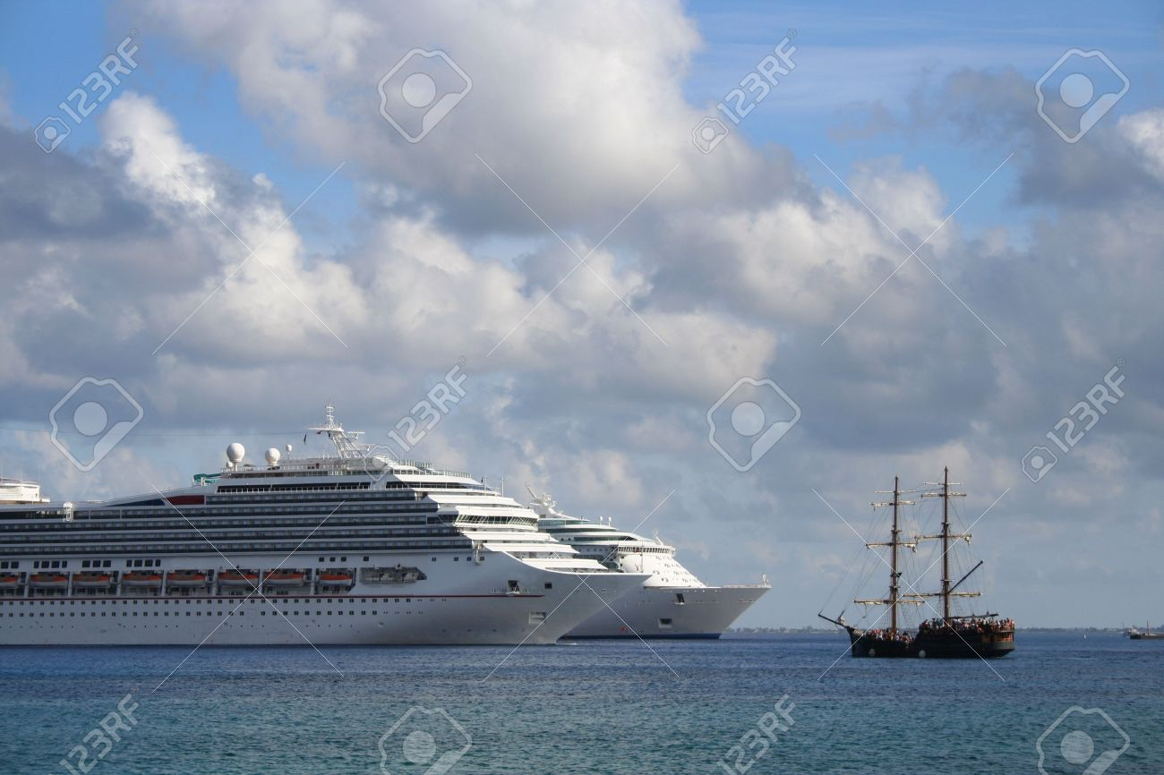 Two modern, huge cruise ships facing a small, old fashioned pirate ship in the Caribbean. Stock Photo - 7616433