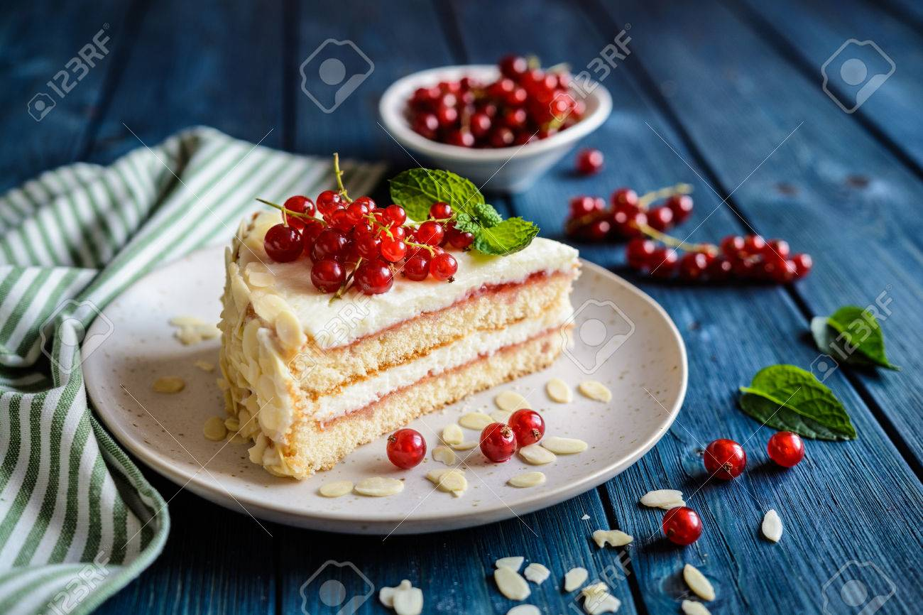 Delicious cake filled with mascarpone, whipped cream, red currant jam and decotated with almond slices - 81639496