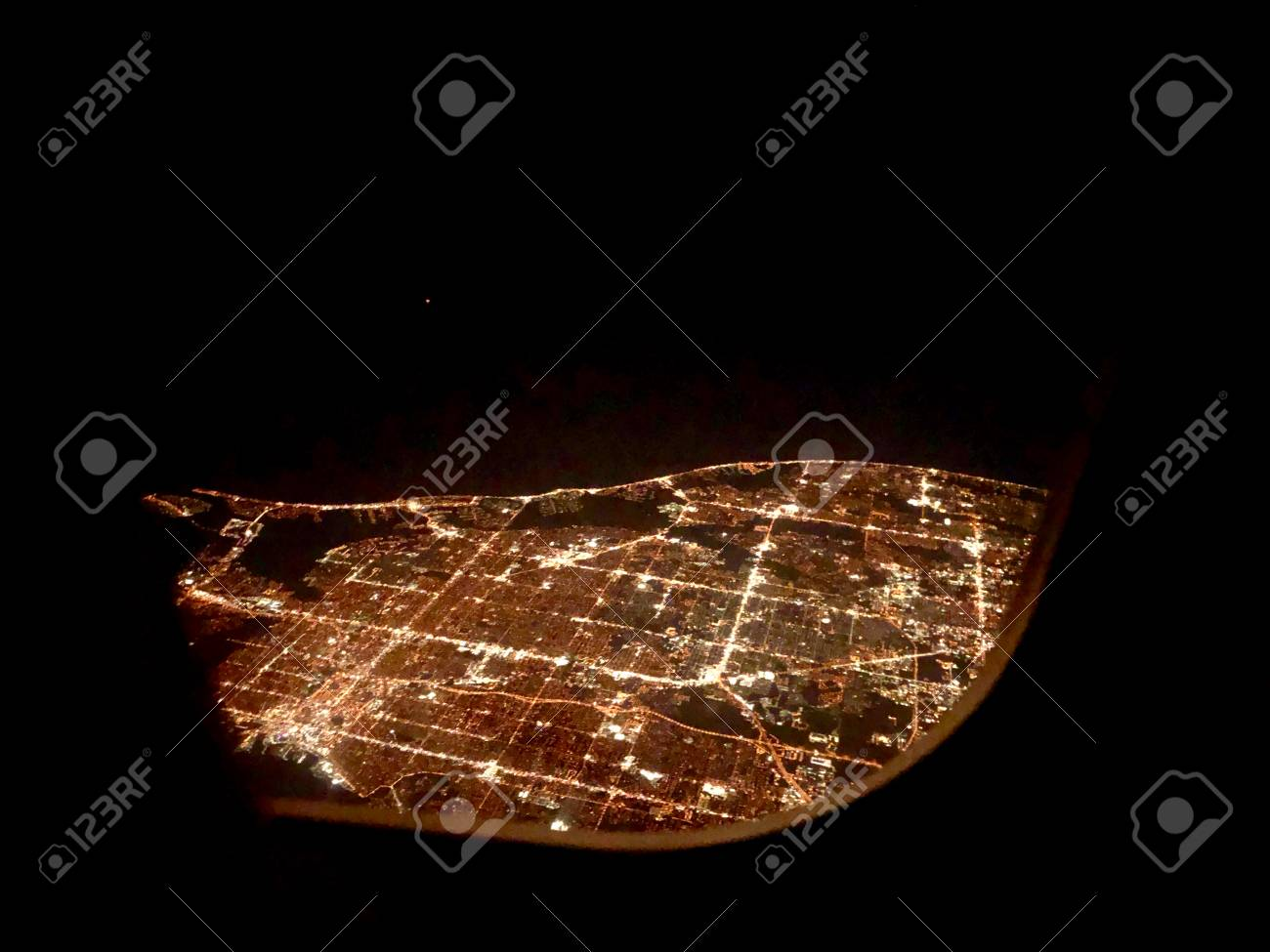 Flying Over A City At Night Looking Lights Through Airplane Window Stock Photo