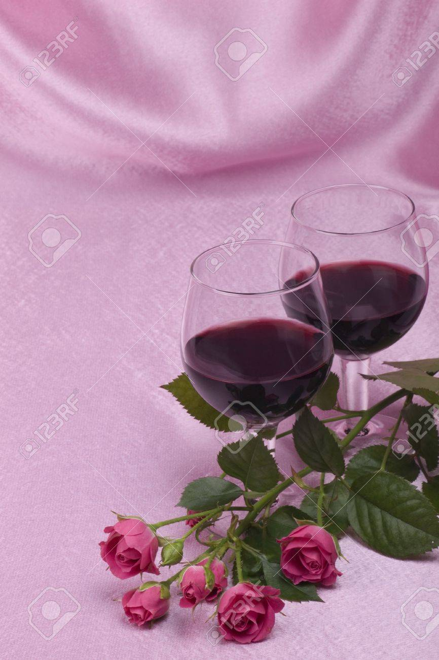 two glass with wine and roses on a pink  background Stock Photo - 7213232