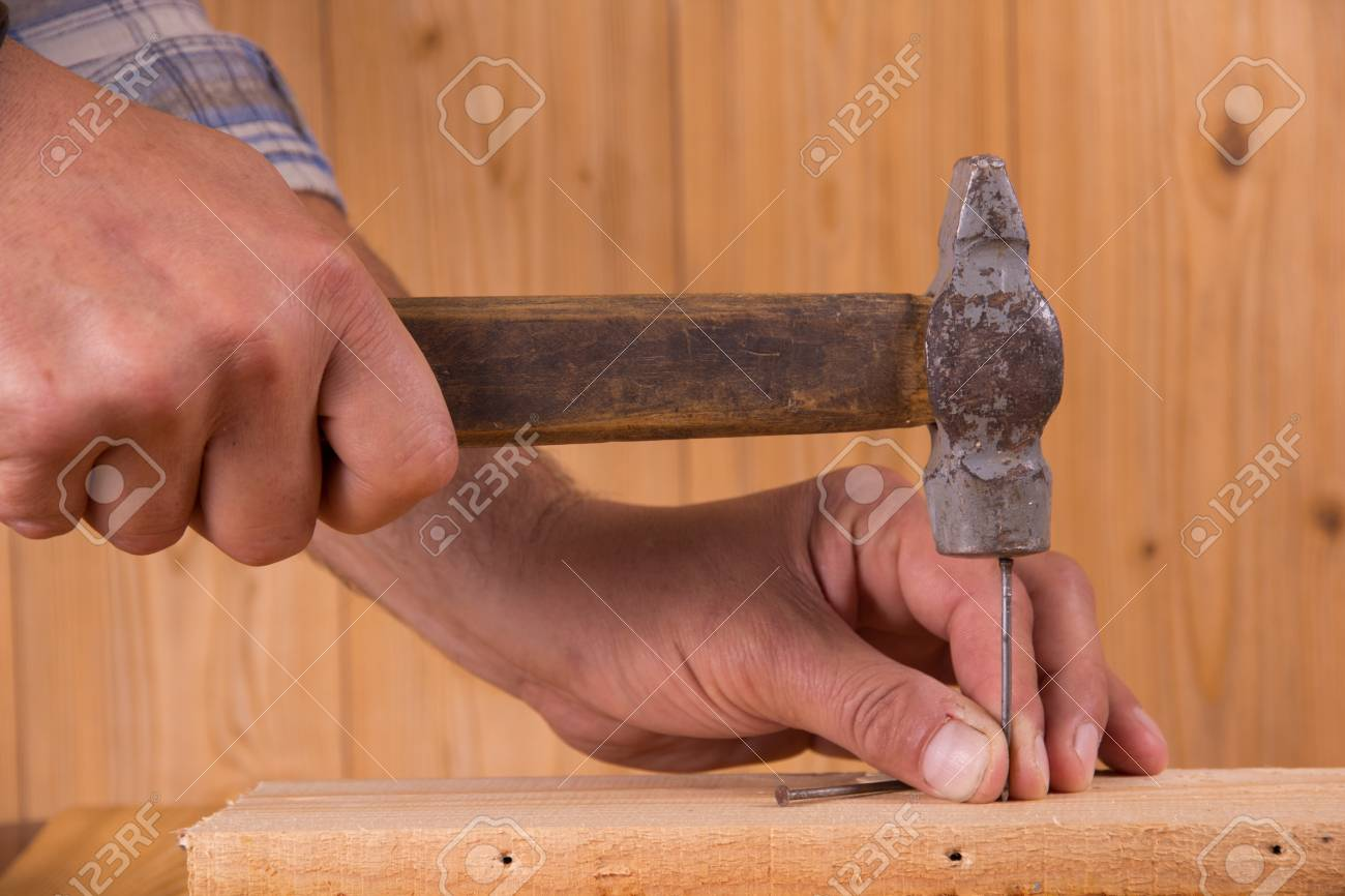 Driving a nail into a board Stock Photo - 15713205