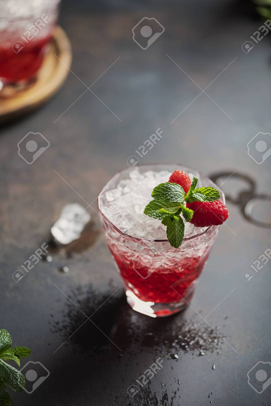 Gradient red cocktail with crushed ice, raspberry and mint, selecrive focus image - 144880211