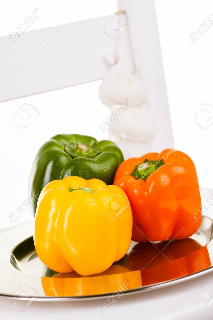 Yellow, orange and green peppers in a silver plate with garlic Stock Photo - 15327735