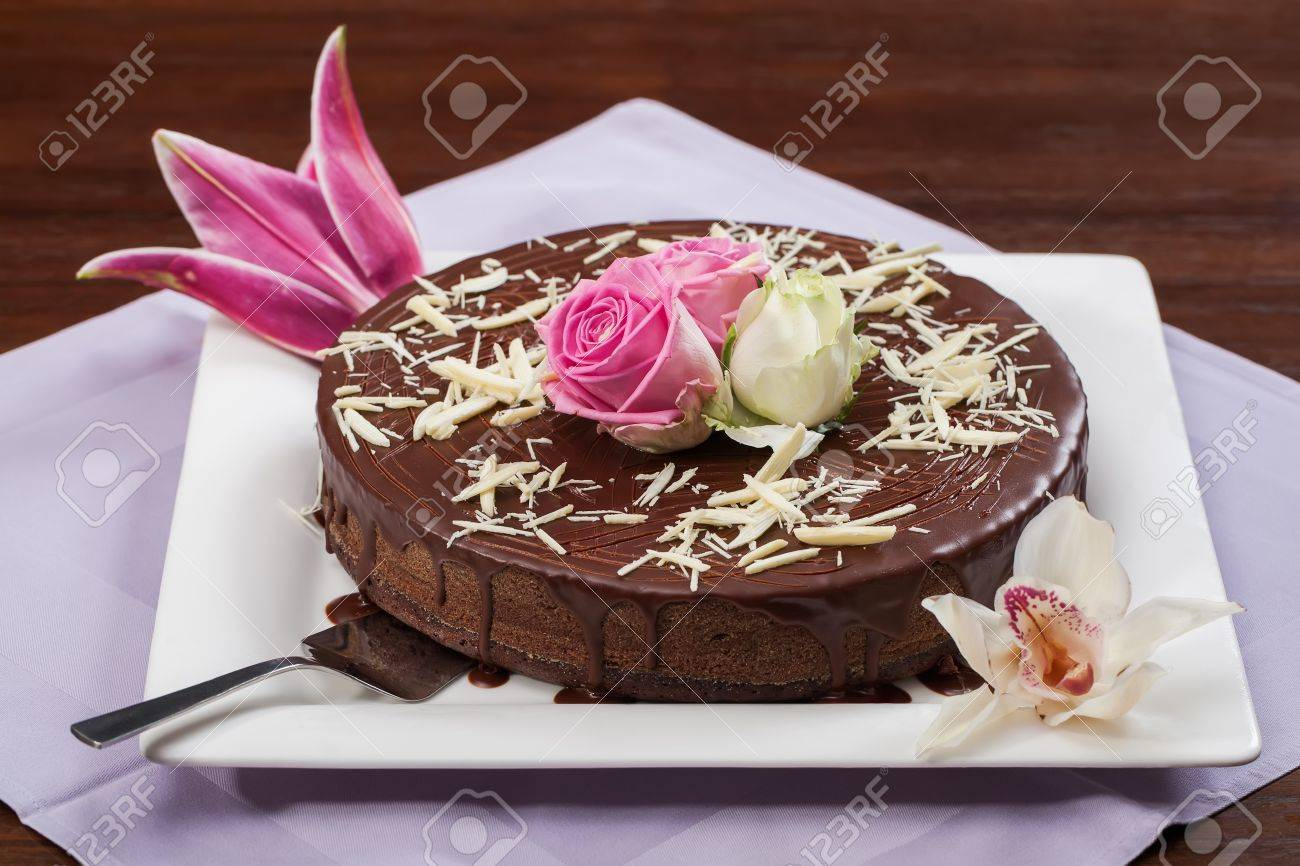 A Big Chocolate Cake With Sauce And Some Flowers. Stock Photo ...