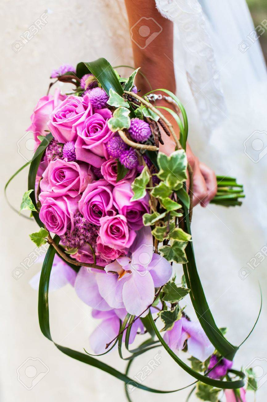 The bride in her wedding dress with her beautiful bouquet filled with pink roses and orchads. Stock Photo - 17222895