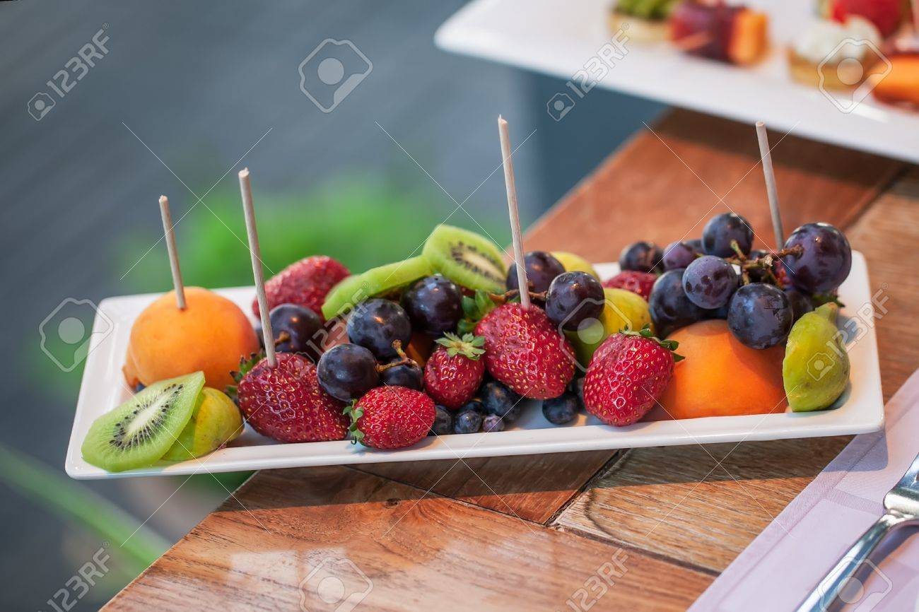 Plate filled with peaches, kiwi, red grapes and strawberries. Stock Photo - 17222759