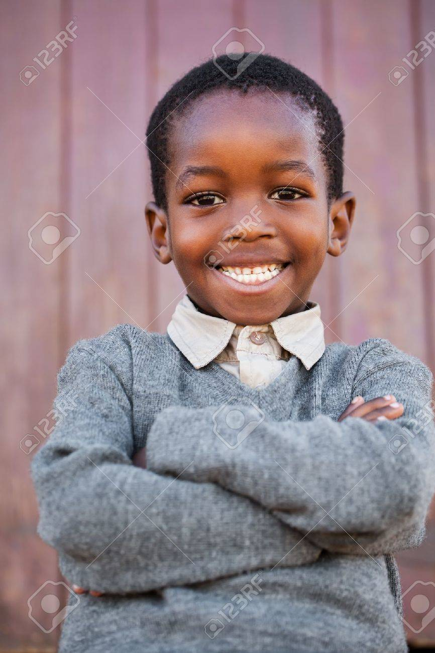 A friendly school boy with crossed arms before the classroom Stock Photo - 20359660
