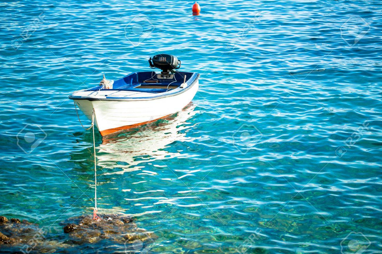A boat floating on the water and anchored to a rock. Stock Photo - 20078789
