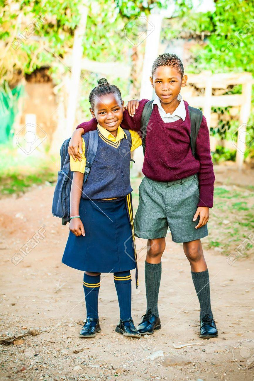 an african older brother proudly standing with his younger sister in their school uniform just before school starts Stock Photo - 20351541
