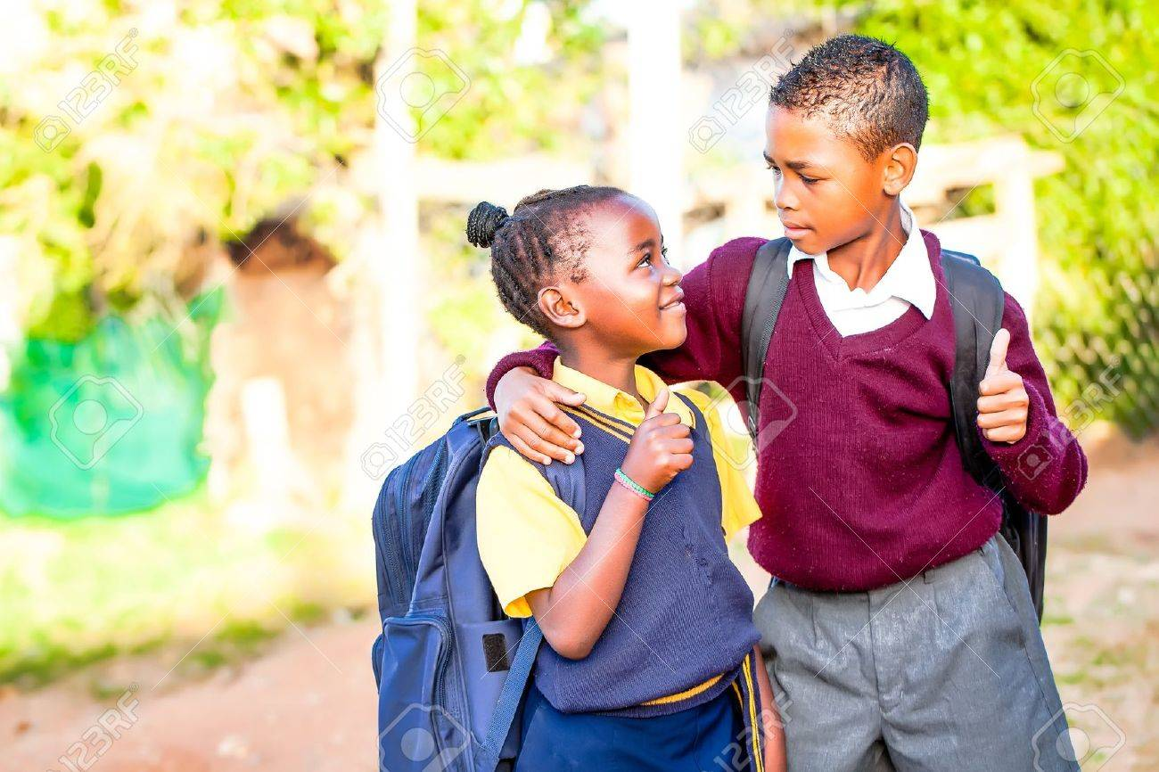 an young african brother with his arm around his younger sister showing positivety with a thumbs up while his younger sister looks up at him in adoration and pride Stock Photo - 20351560