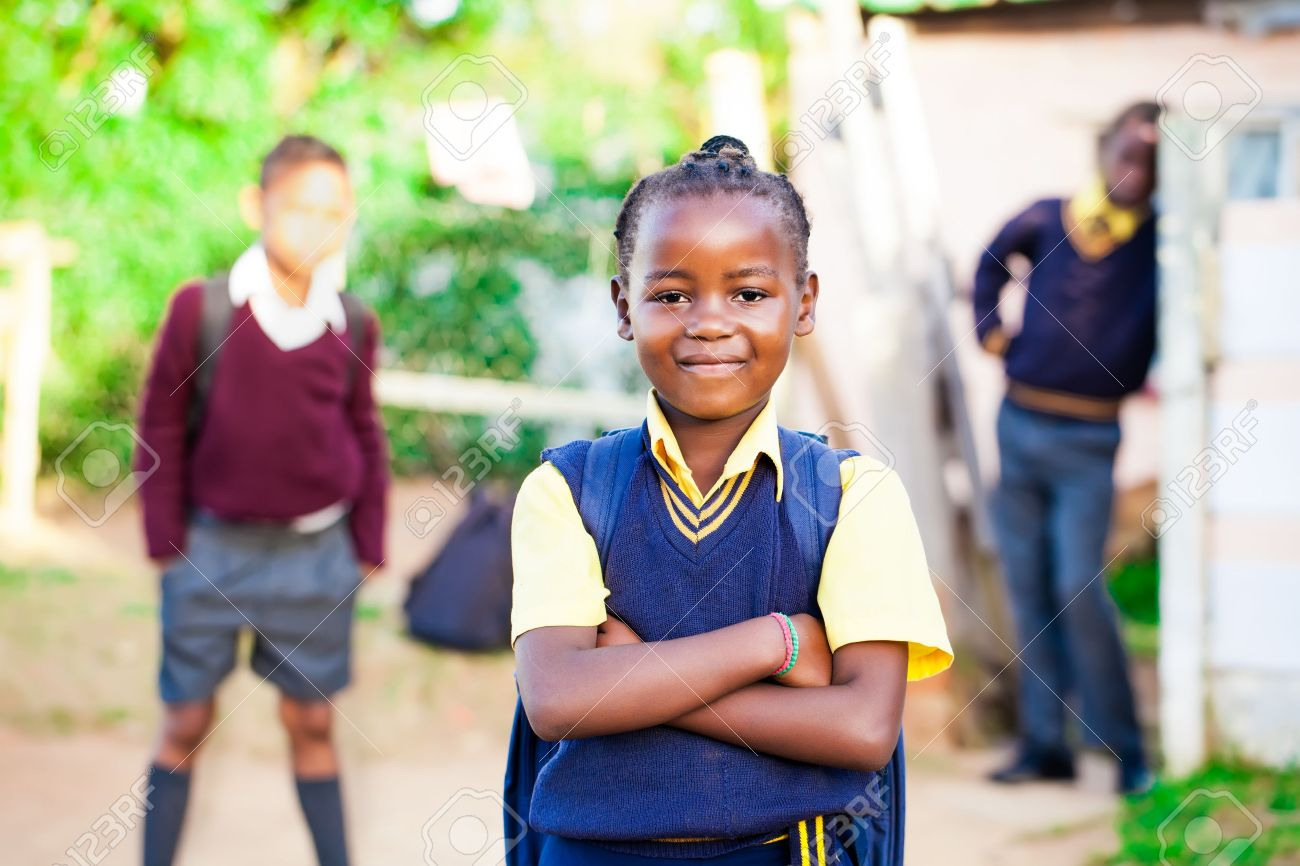 pretty young african girl standing proud in her yellow and blue school uniform with siblings watching over her Stock Photo - 20351546