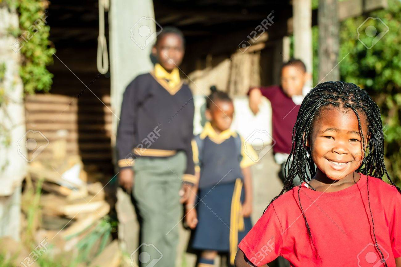 a pretty african girl with braided hair and a bright red shirt smiling confidently with her siblings in the backround watching over her Stock Photo - 20359699