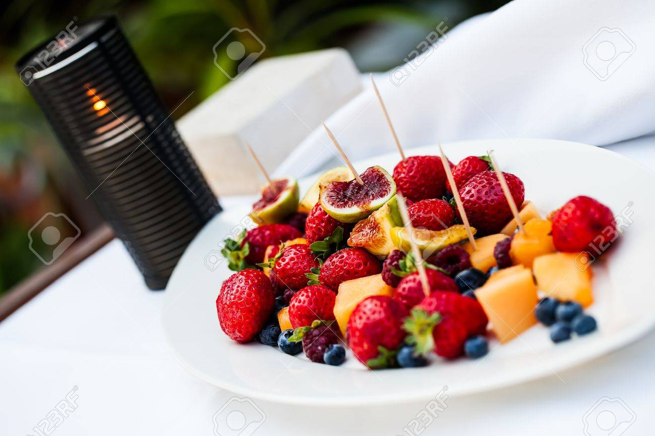 image of a porcelain plate filled with various fresh fruits and finger sticks on a white table and a burning candle in the background Stock Photo - 21532998