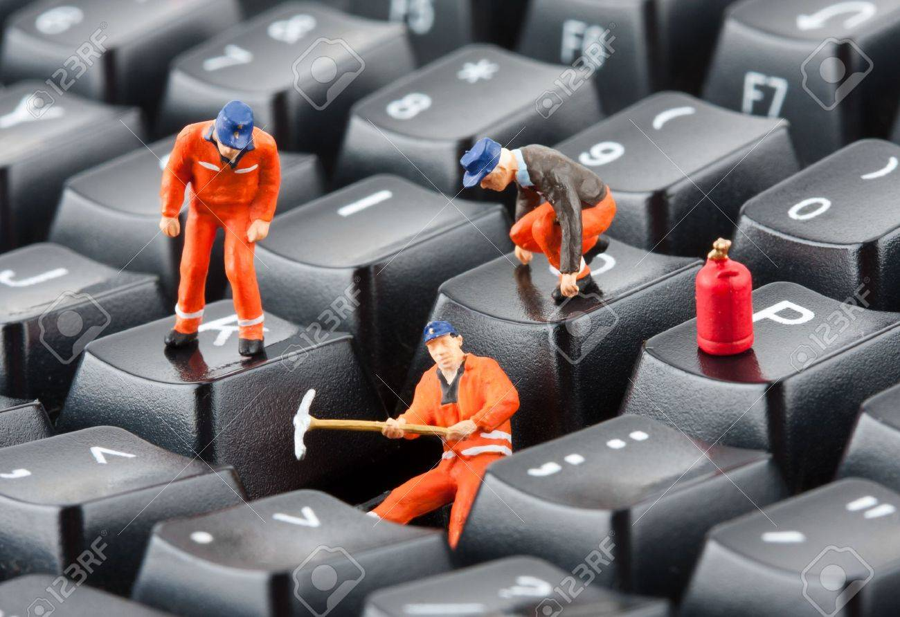 Small figurines of workers repairing computer keyboard Stock Photo - 18055894