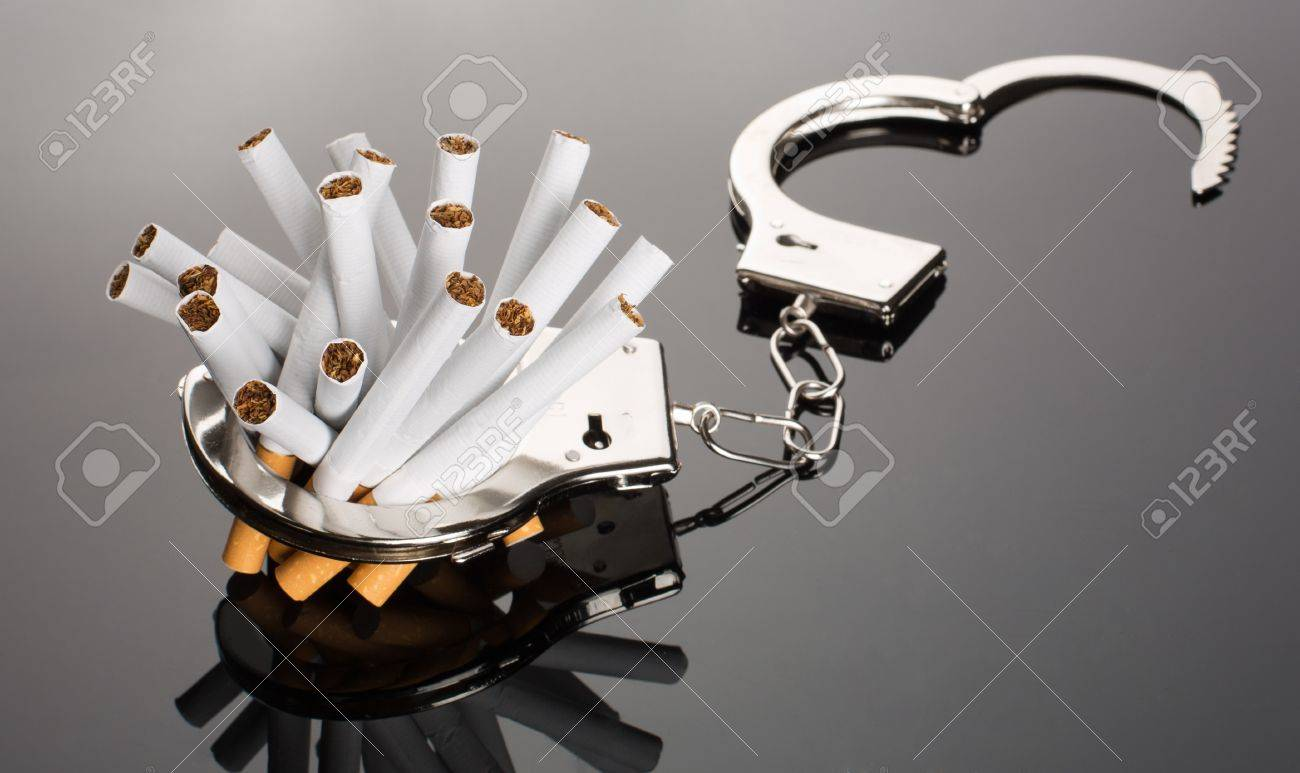 Heap of cigarettes locked to handcuffs Stock Photo - 18072705