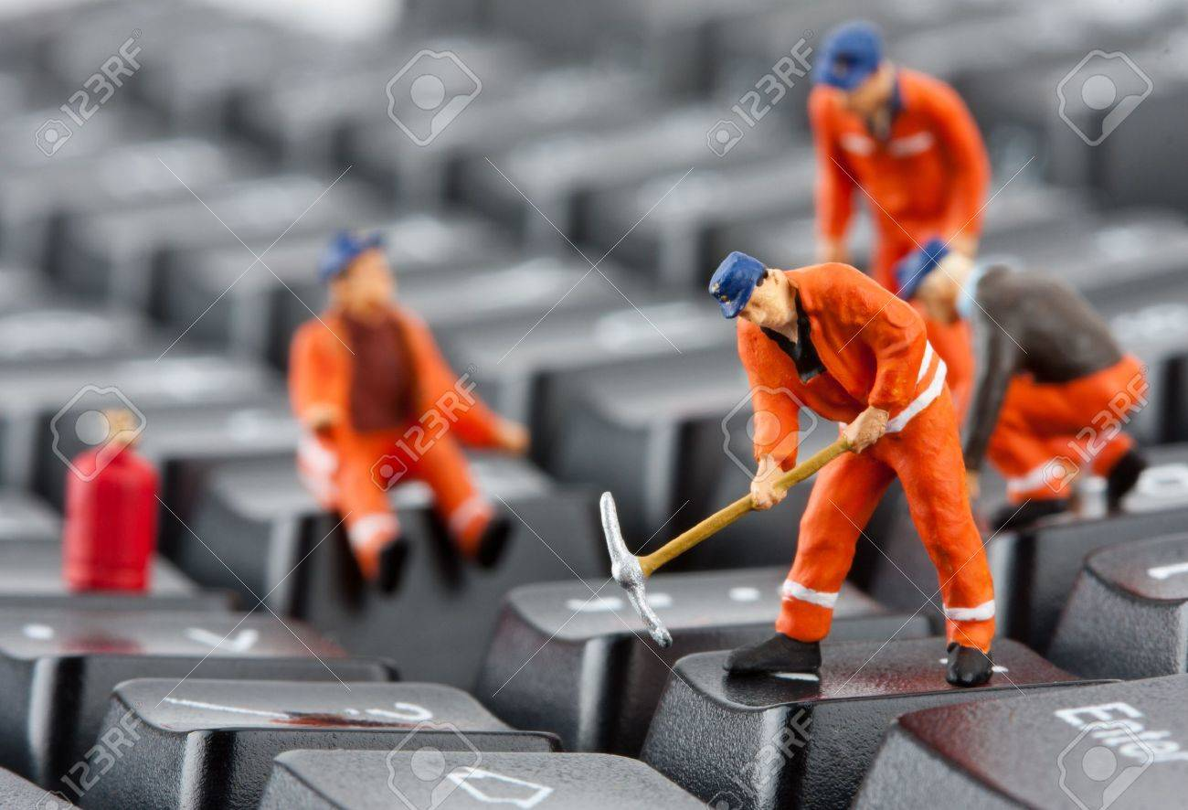 Small figurines of workers repairing computer keyboard Stock Photo - 18104125