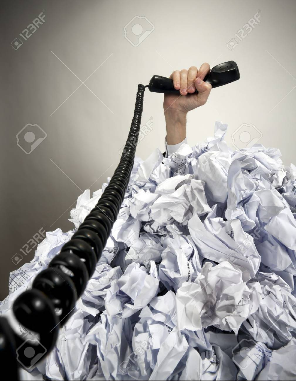 Hand with phone reaches out from big heap of crumpled papers Stock Photo - 18312385