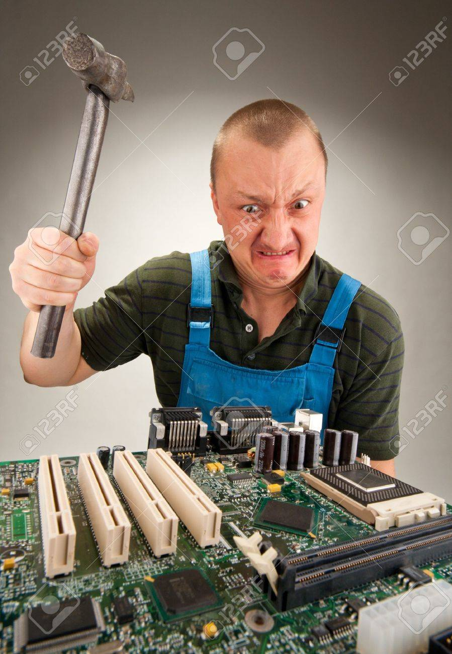 Mad IT worker repairing computer circuits by hammer Stock Photo - 40733369