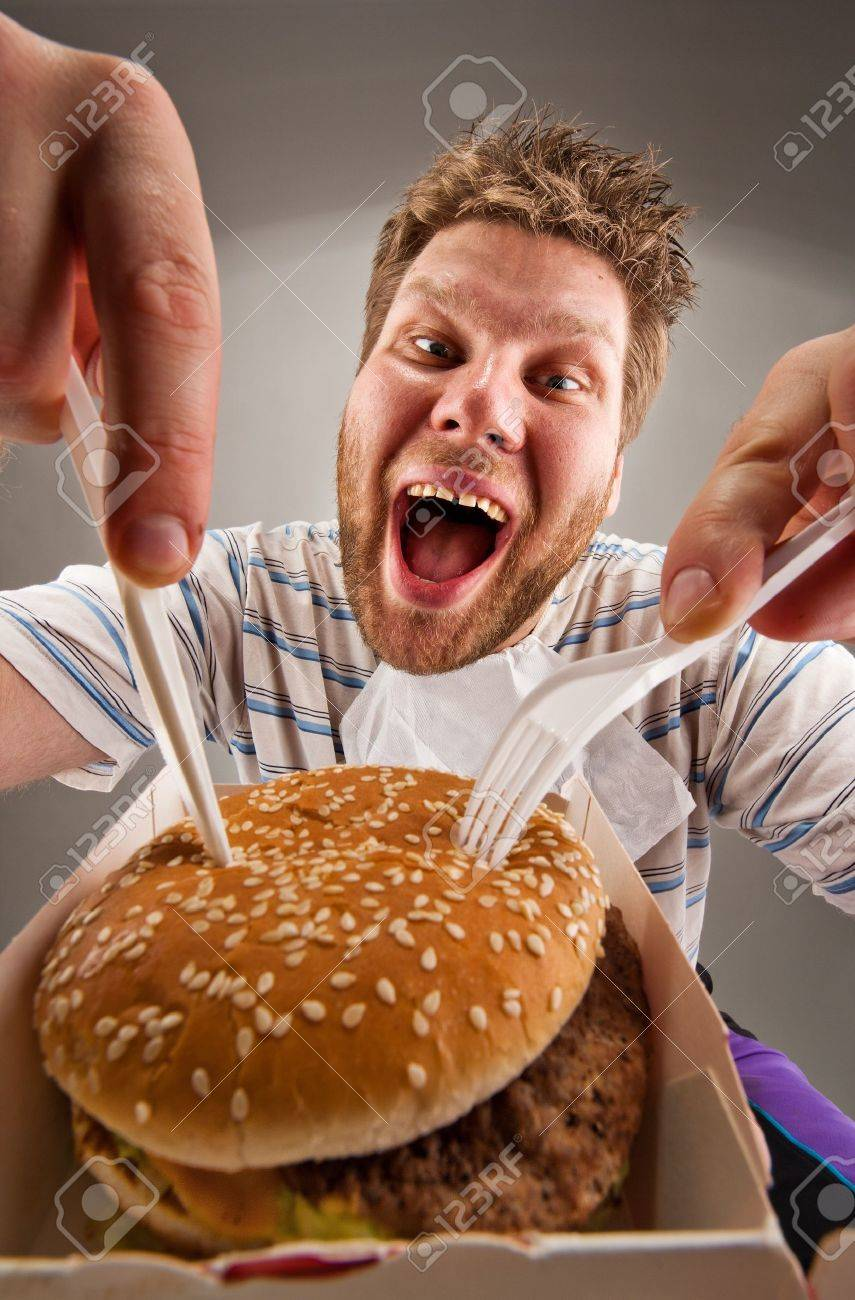 Portrait of happy man with knife and fork eating burger Stock Photo - 18400442