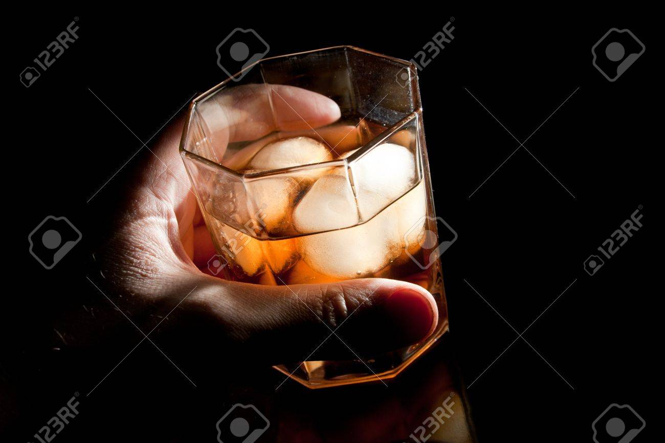 Gold whiskey on the rocks in alcoholic's hand Stock Photo - 18426976