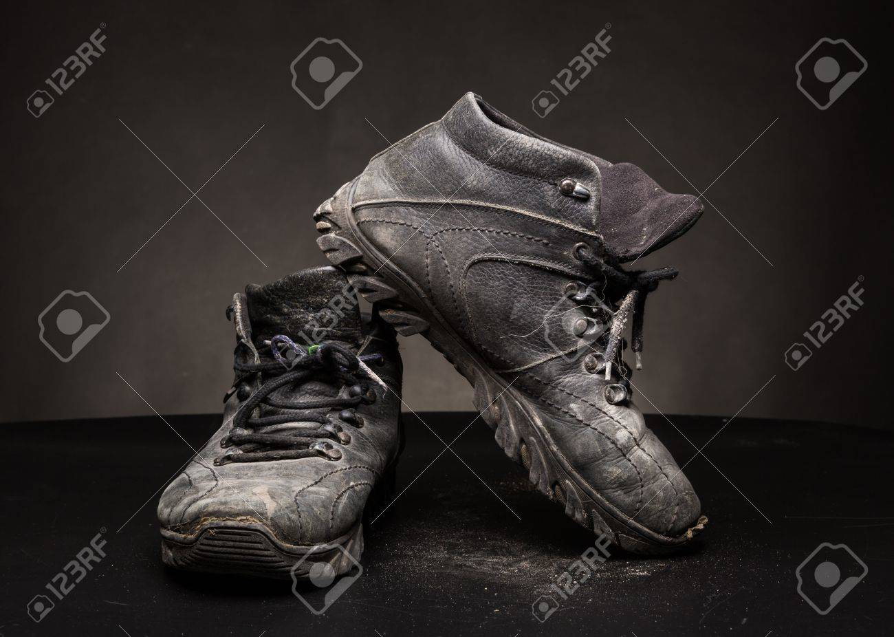 A pair of old black worn out shoes on the floor
