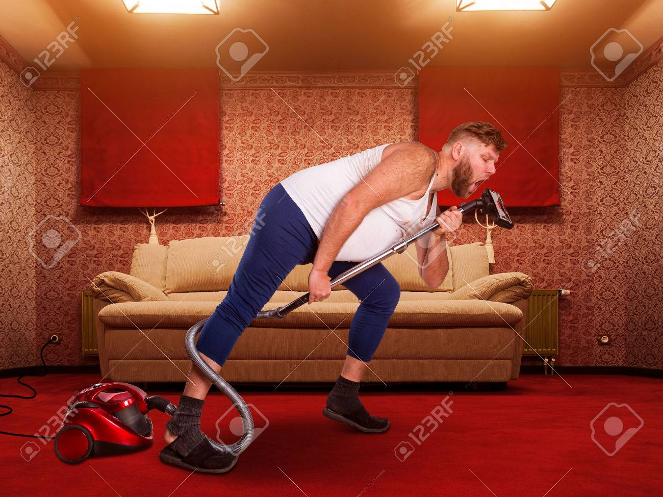 Adult man sings to the vacuum cleaner at home interior Stock Photo - 38337853