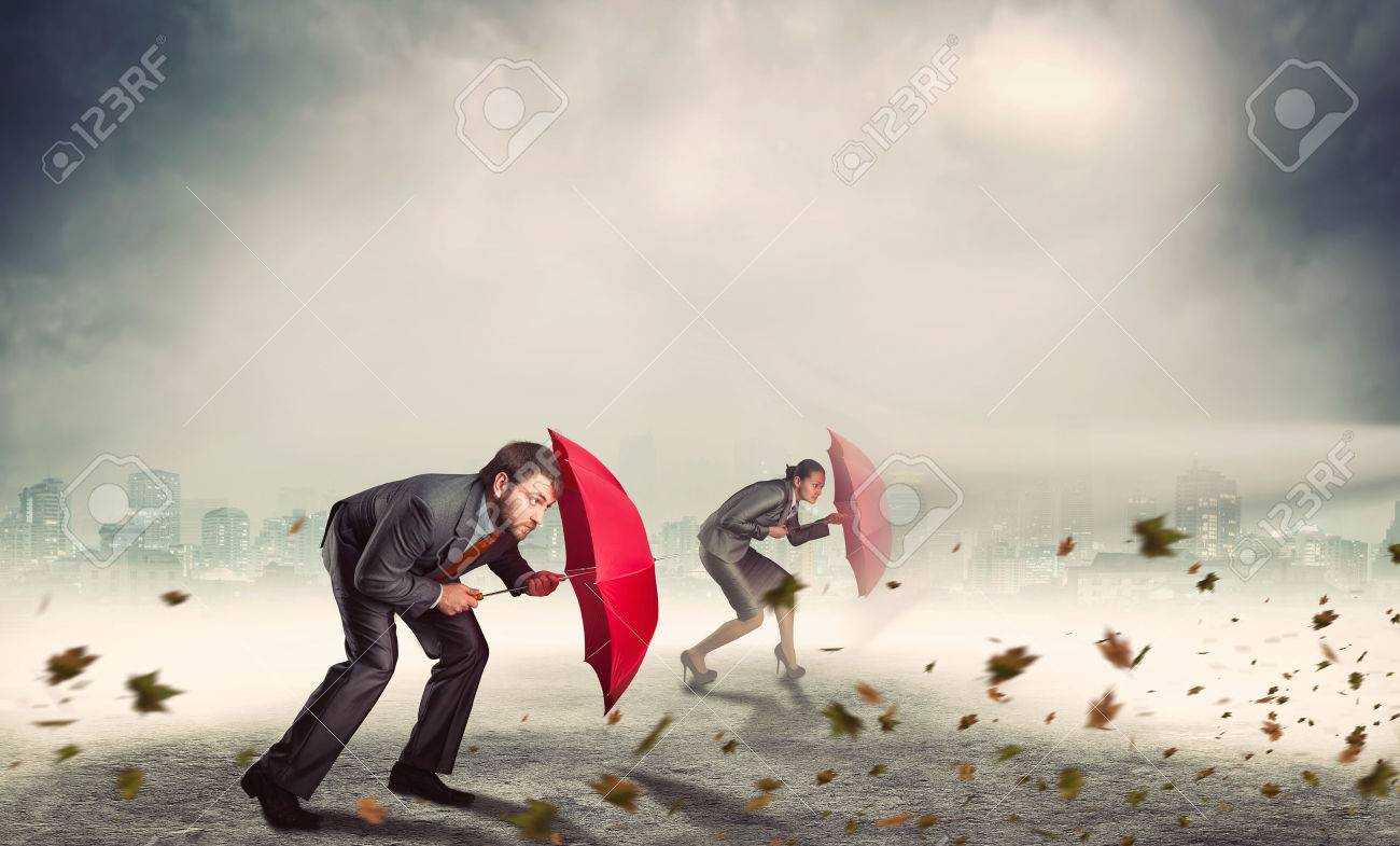 Businessman and businesswoman protect themselves from rocks with umbrella in storm Stock Photo - 38834746