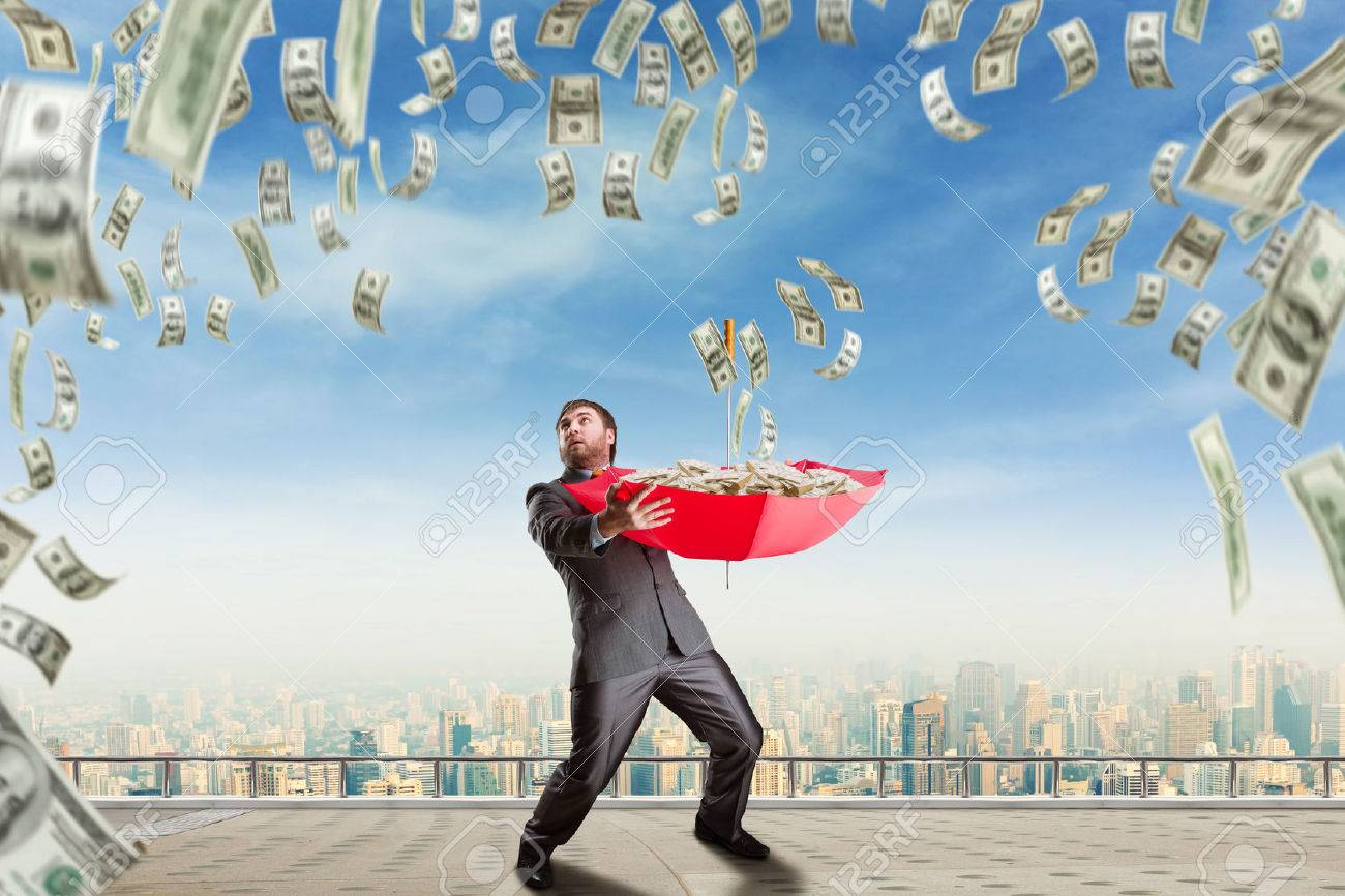 Businessman with umbrella full of money and money are falling Stock Photo - 39183650