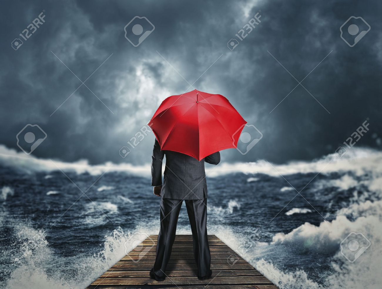 Man with red umbrella standing back on the pier at night storm Stock Photo - 39184554