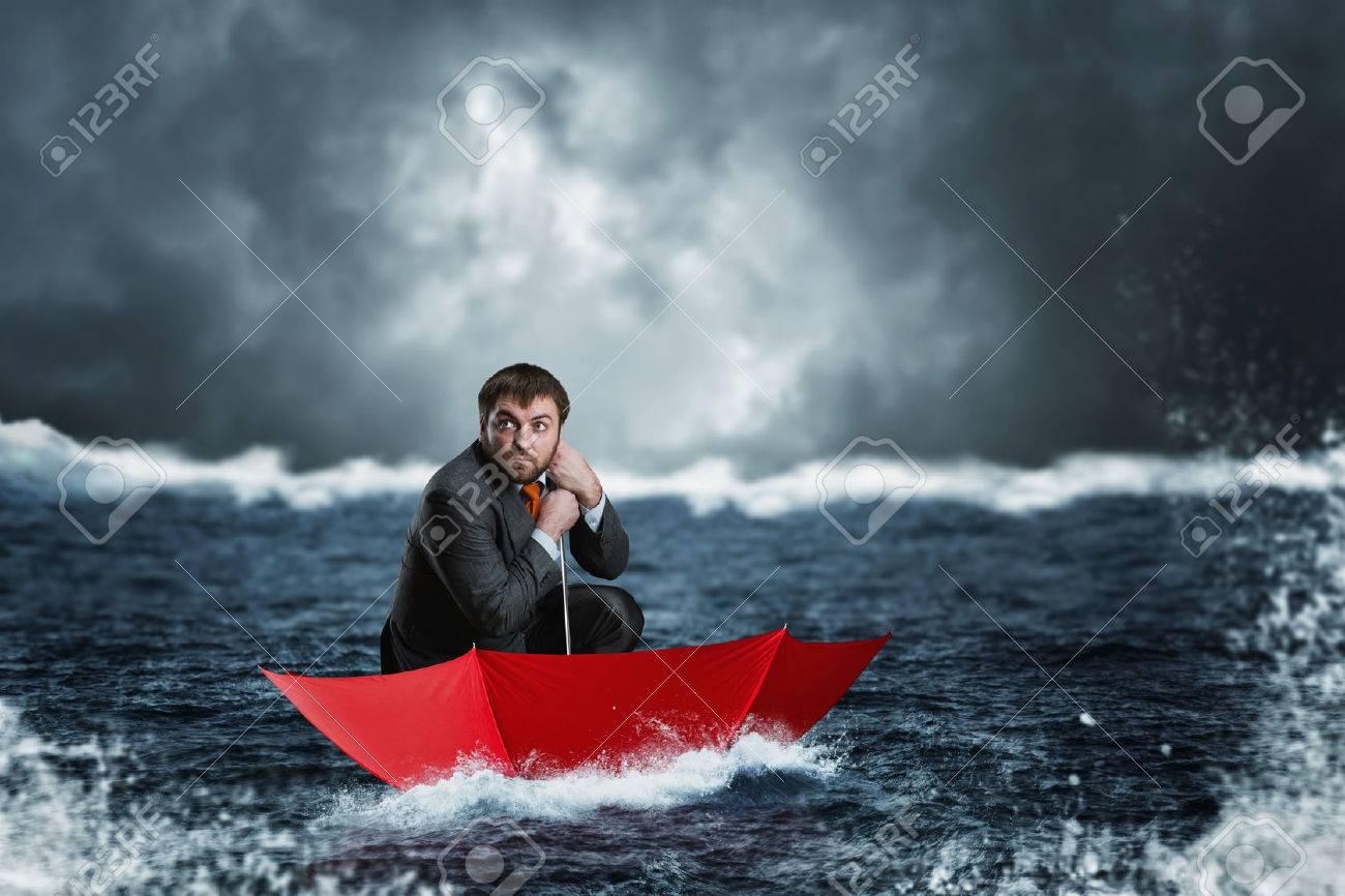 Scared businessman in the umbrella sails in the sea in the night Stock Photo - 39184558