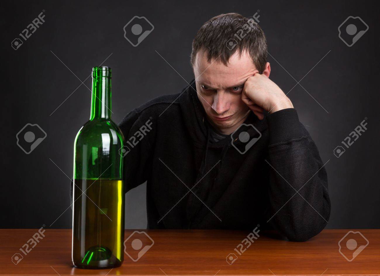39184899-sad-man-looks-at-the-bottle-of-