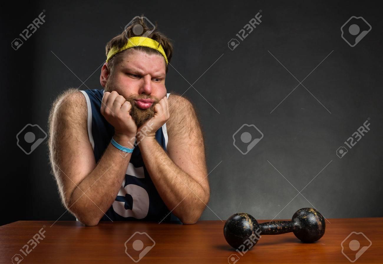 Sad man looking at dumbbell at the table Stock Photo - 40362297