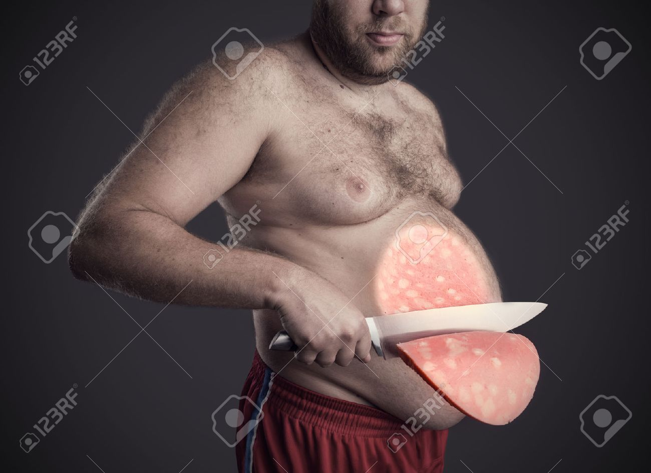 Fat man cuts a big slice of a sausage from his belly over grey Stock Photo - 43776031