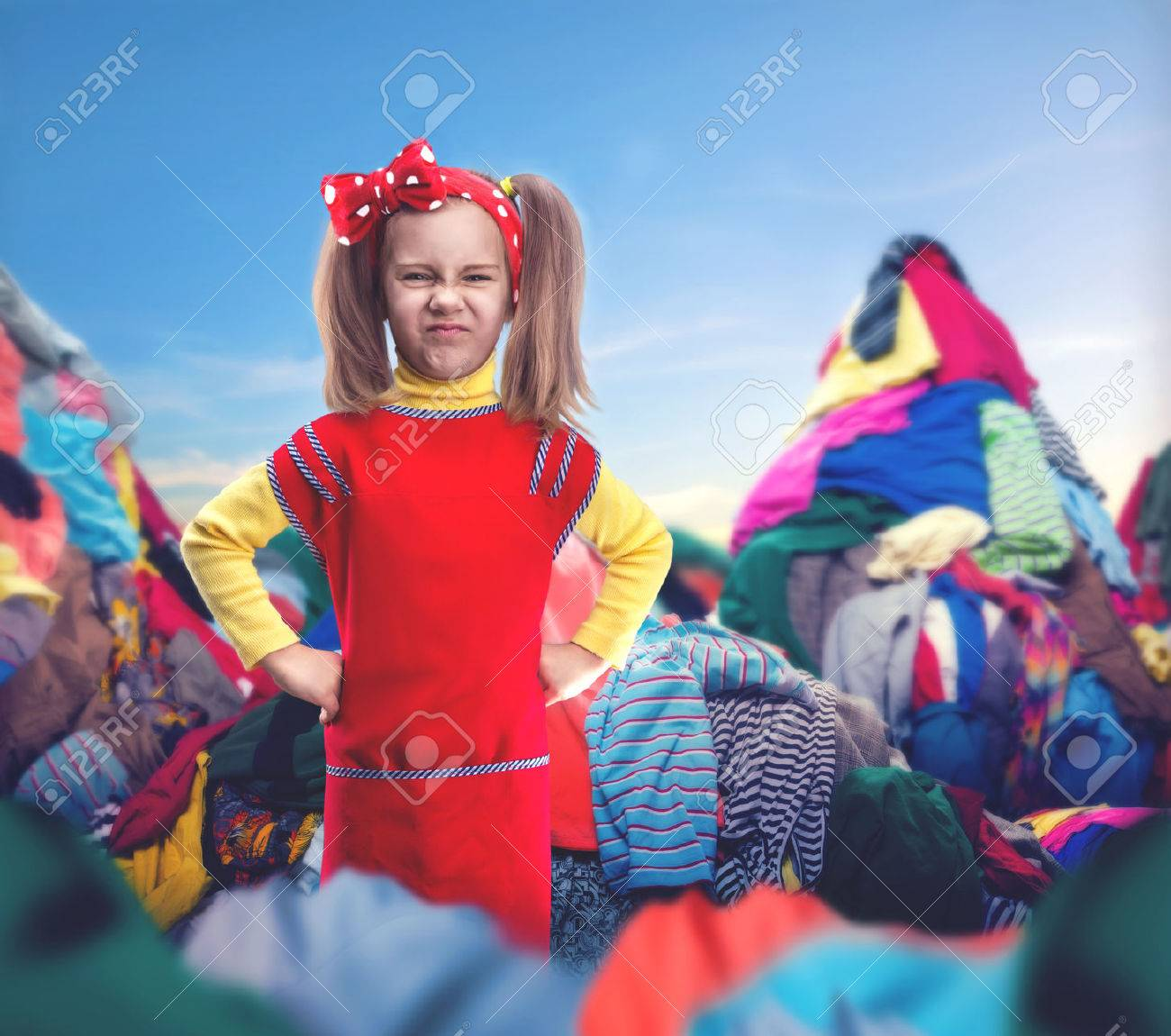 Little girl with her hands on hips stands among heaps of clothes Stock Photo - 44113244