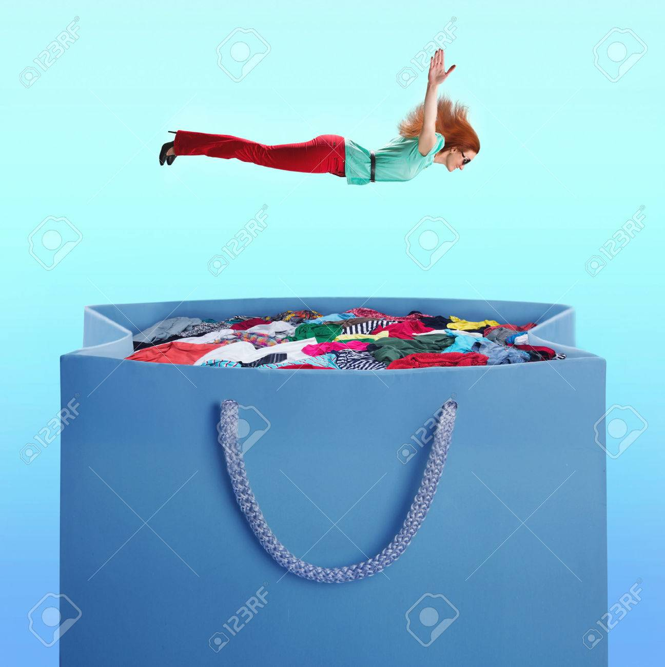 Woman flying to the heap of clothes in the shopping bag over blue - 44360040