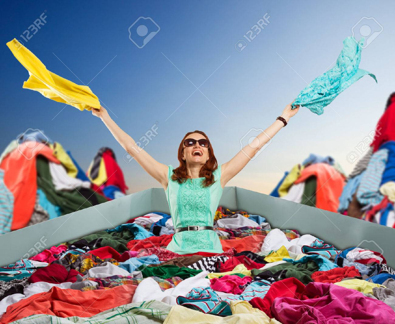 Young happy woman in sunglasses sits in the shopping bag among a big heap of clothes flinging things out Stock Photo - 44360044