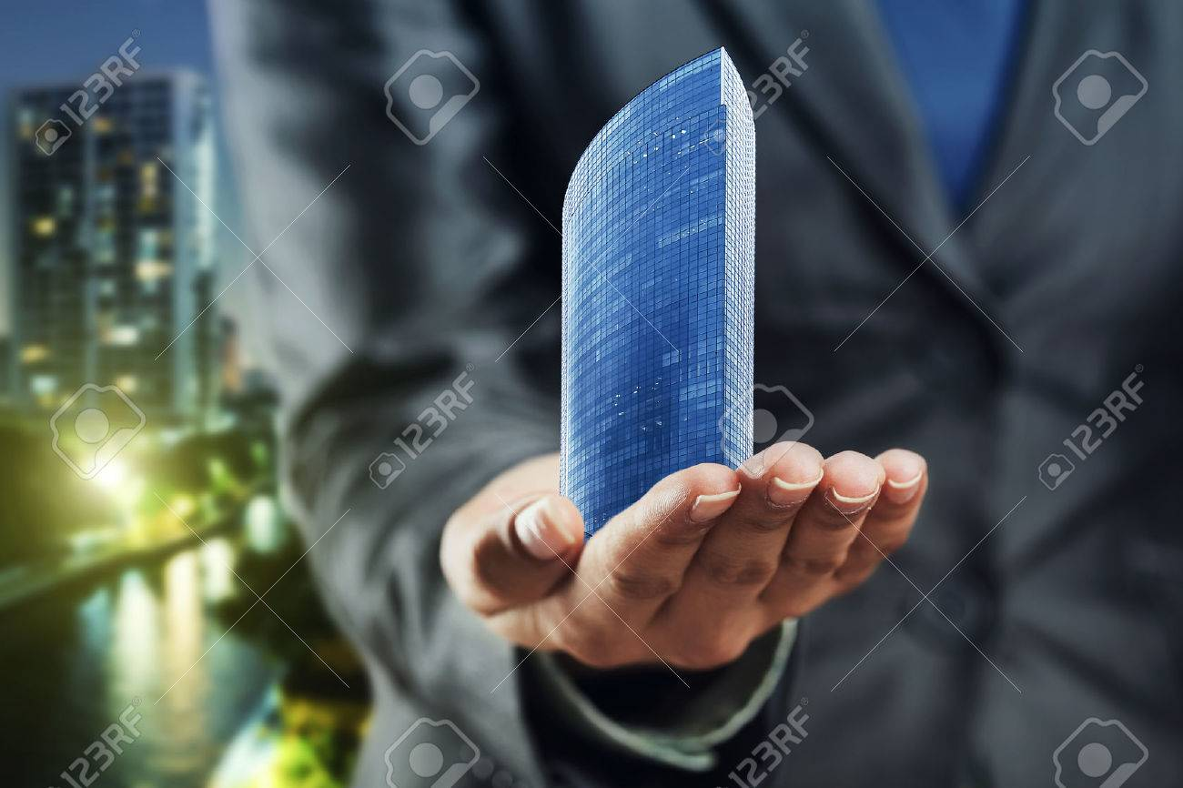 Small office building standing on the human palm Stock Photo - 45587392