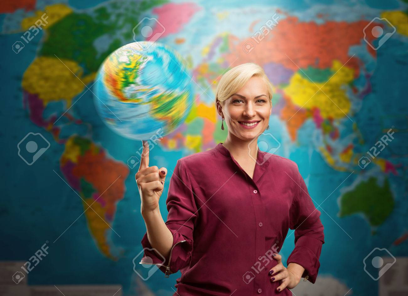Travel agent woman with a globe against a map of the world Stock Photo - 47997614