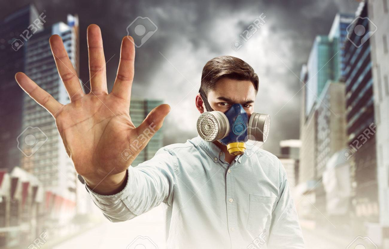 Young man in gas-mask in night town with atmospheric pollution shows stop hand sign - 54108963