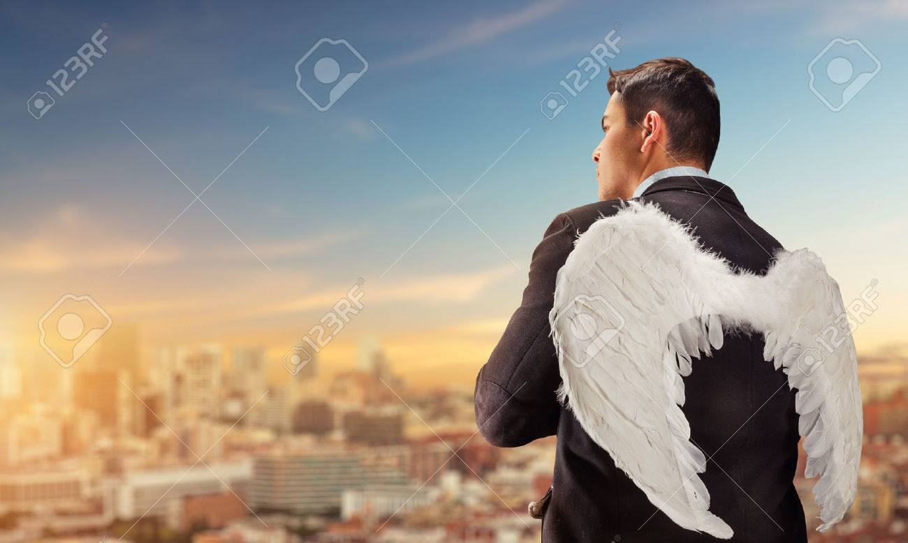 Businessman with angel wings on his back looking at the city - 54108964