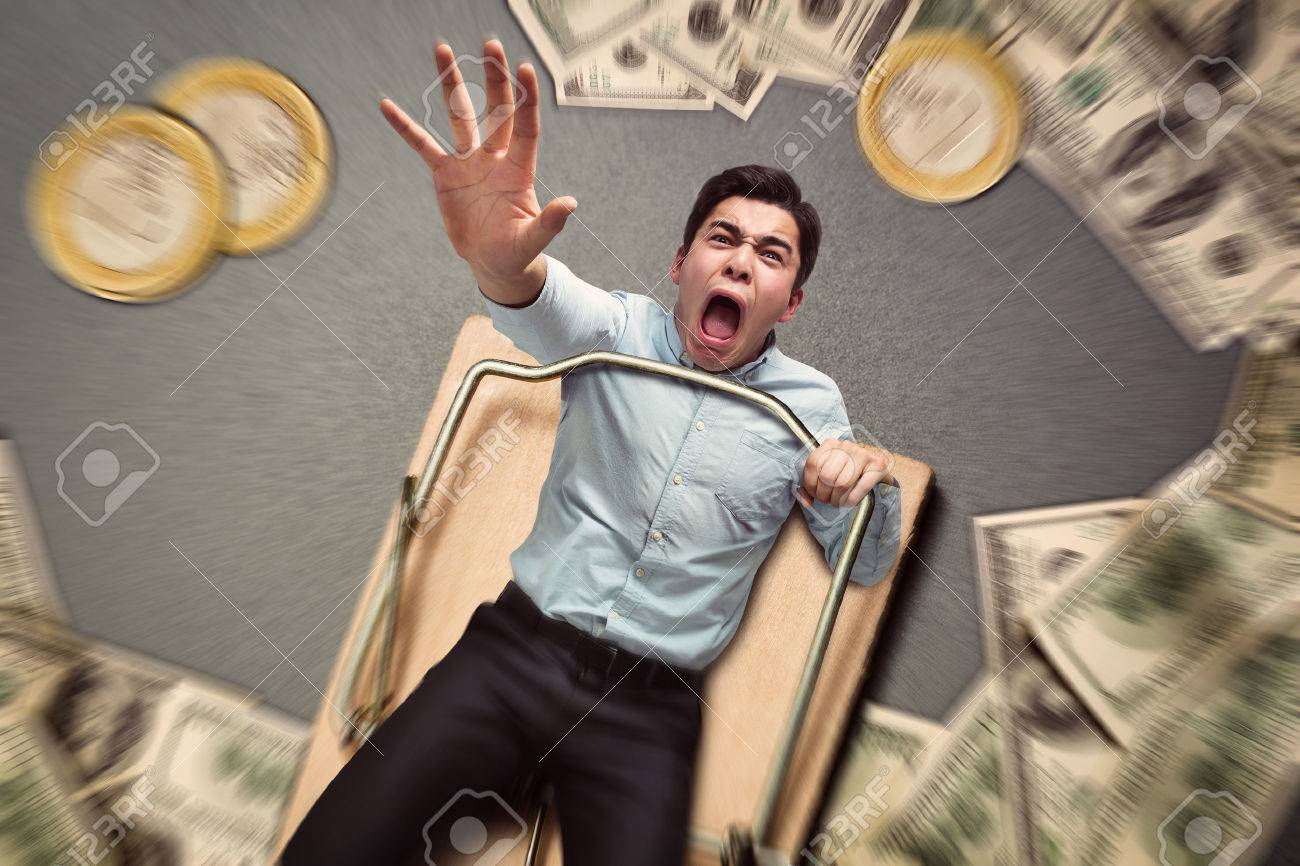 Young businessman in a mouse trap with money falling Stock Photo - 55861551