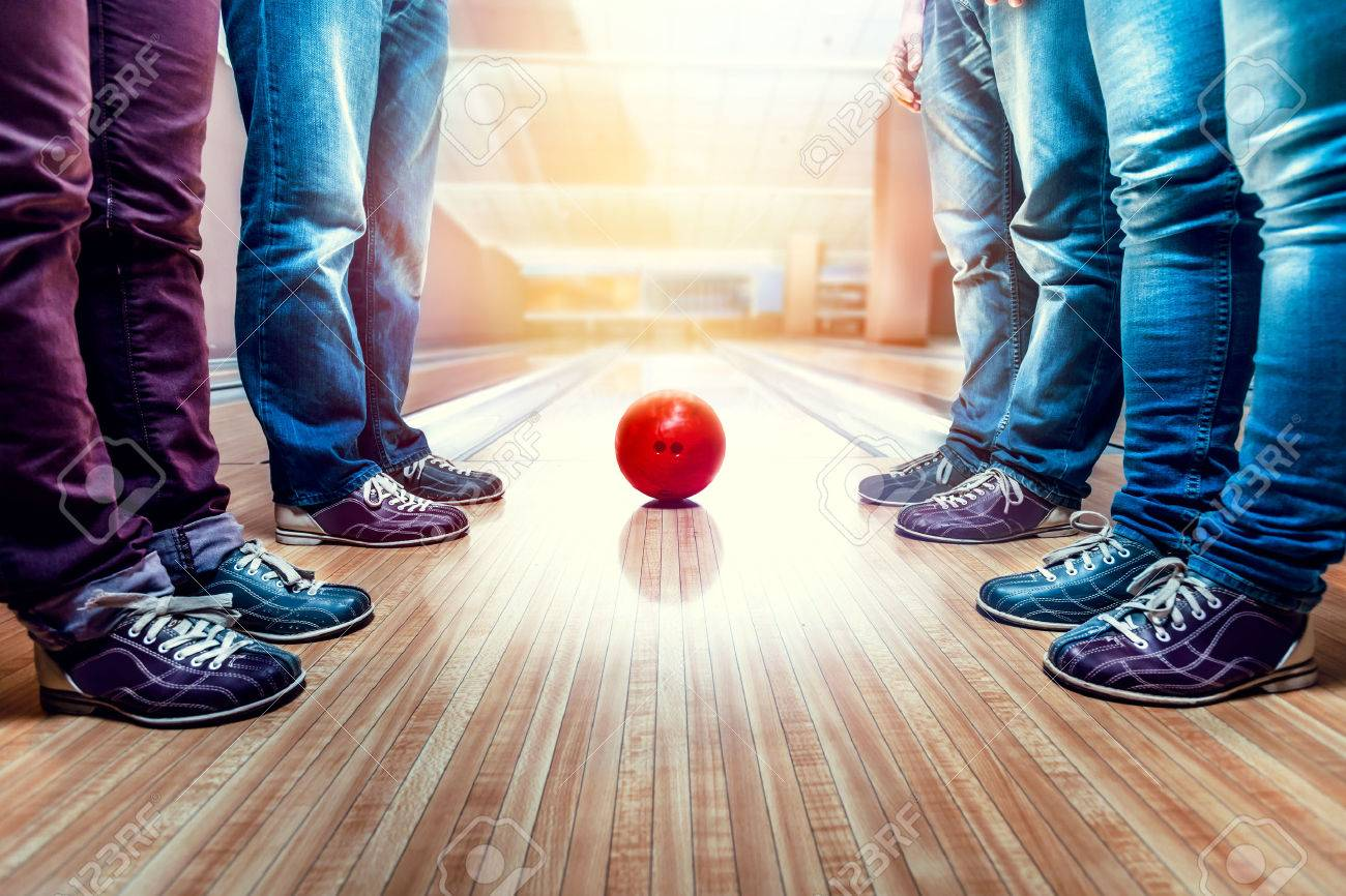 Many people standing near bowling ball on the lane - 63486204