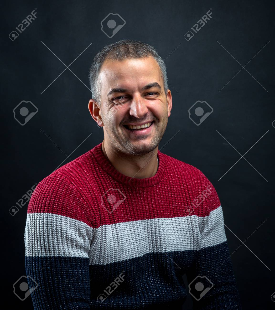 Portrait of smiling man in pullover isolated on black background. Brutal unshaven handsome man in professional studio. - 66901351
