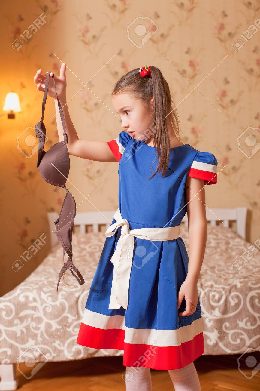 af6fc48240 Stock Photo - Surprised little girl holds a bra in hand. Bedroom on the  background.