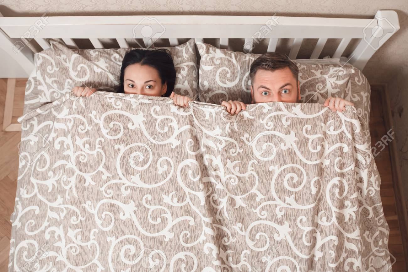 Stock Photo   Young couple peeping from bedsheet at bedroom. Young Couple Peeping From Bedsheet At Bedroom  Stock Photo