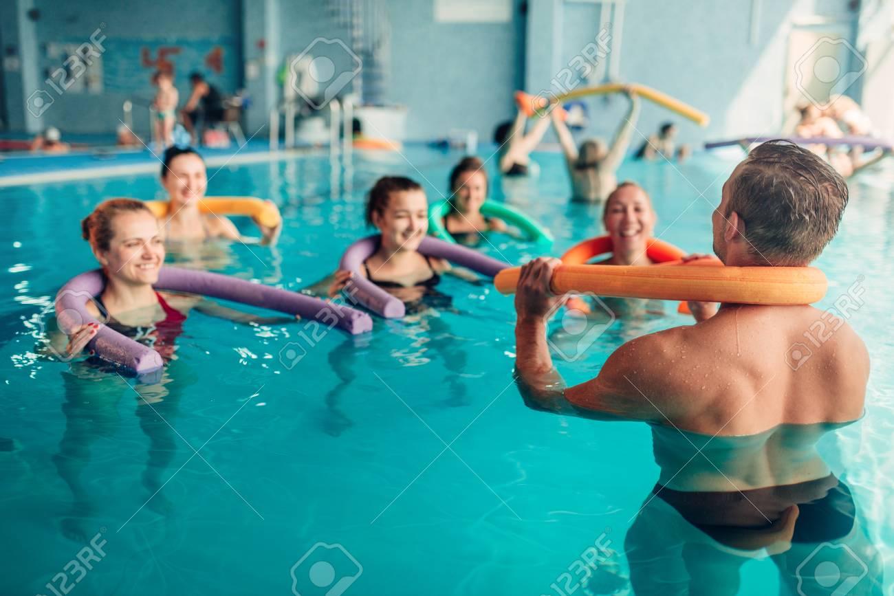 aqua aerobics exercises women with male trainer stock photo