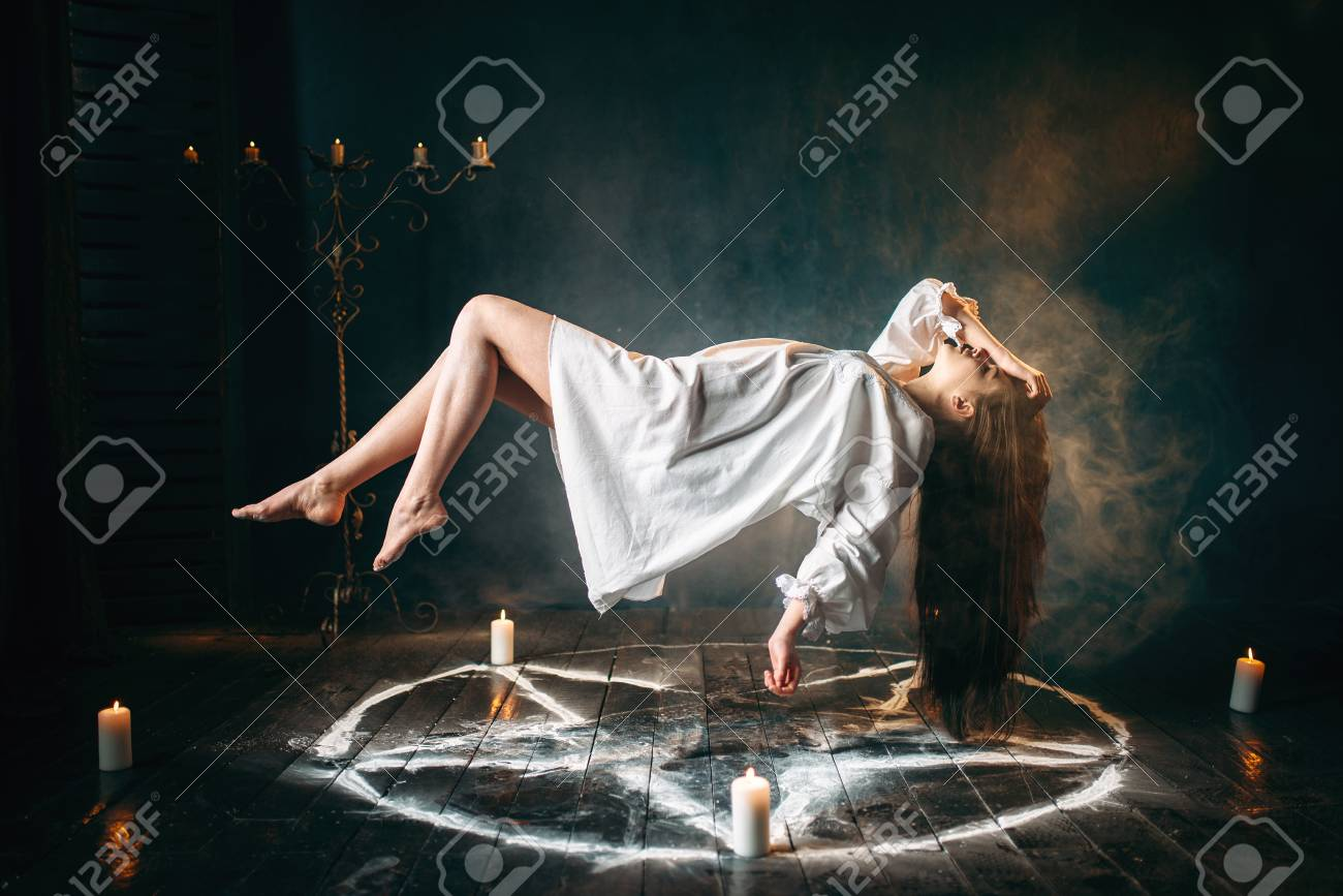 Woman in white shirt flying over pentagram circle - 99438112