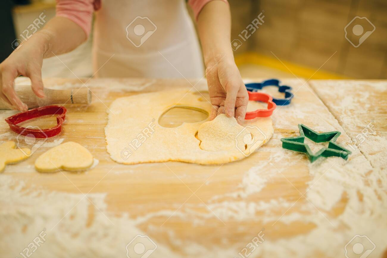 Little girl makes cookies in the shape of a heart - 124377221