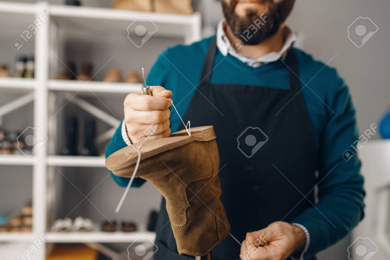 Shoemaker stitches the shoe, footwear repair service. Craftsman skill, shoemaking workshop, master works with boots - 136061935