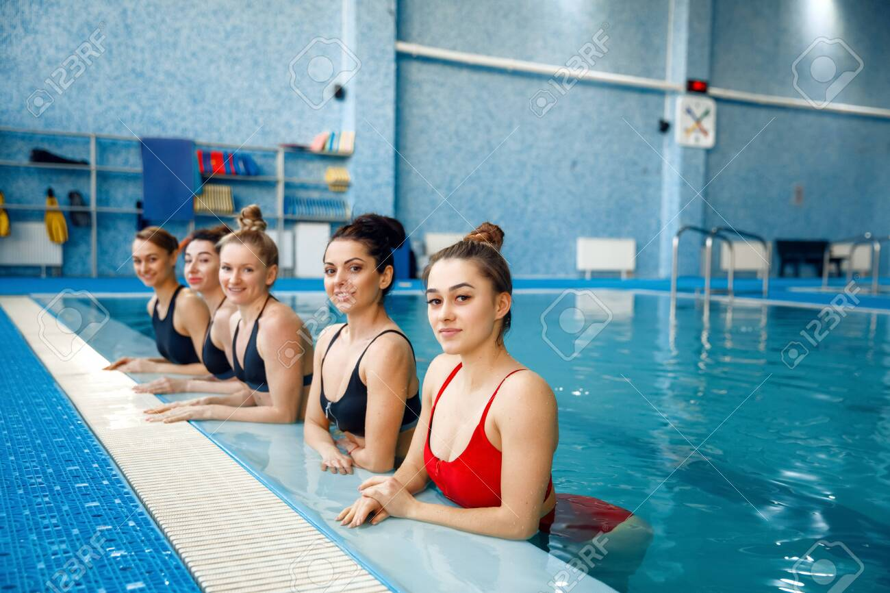 Female swimmers group poses at the poolside - 143942897